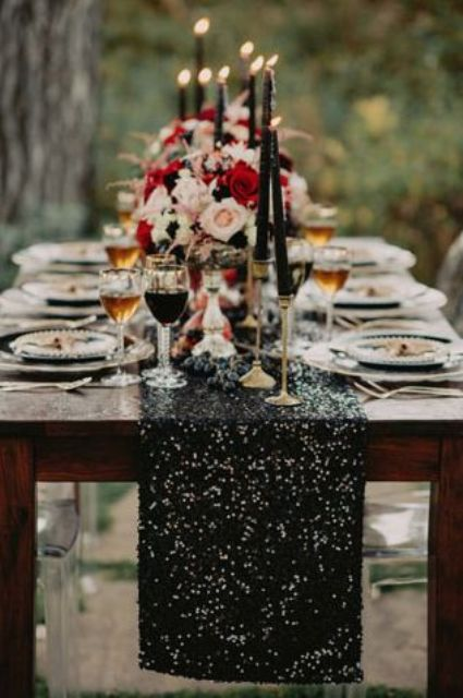 a black sequin table runner, black candles and little blooms for a bold moody wedding tablescape