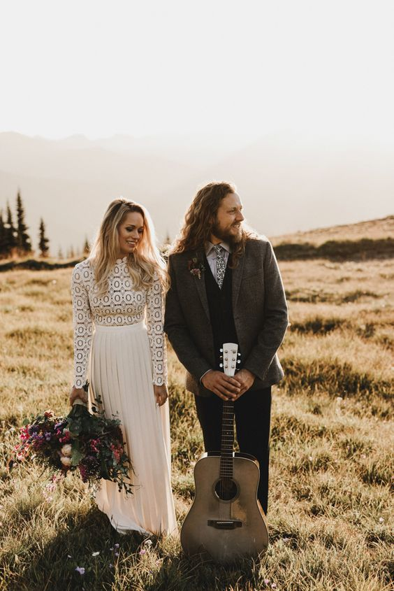 a boho couple with a groom wearing eye-catchy layered attire and a bride rocking a lace top and a pleated skirt