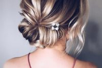 14 a low twisted chignon with a bump, some locks down and little blooms tucked in