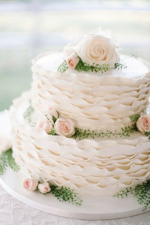 a sweet white ruffled wedding cake with blush and white roses and greenery