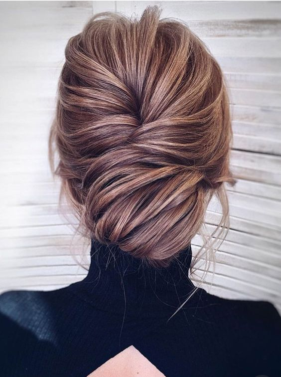 a chic and refined voluminous low bun with a bump and some locks down for pure elegance