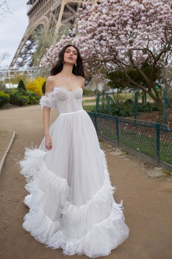 a light and airy draped A-line wedding gown with a sweetheart neckline and feather detailing