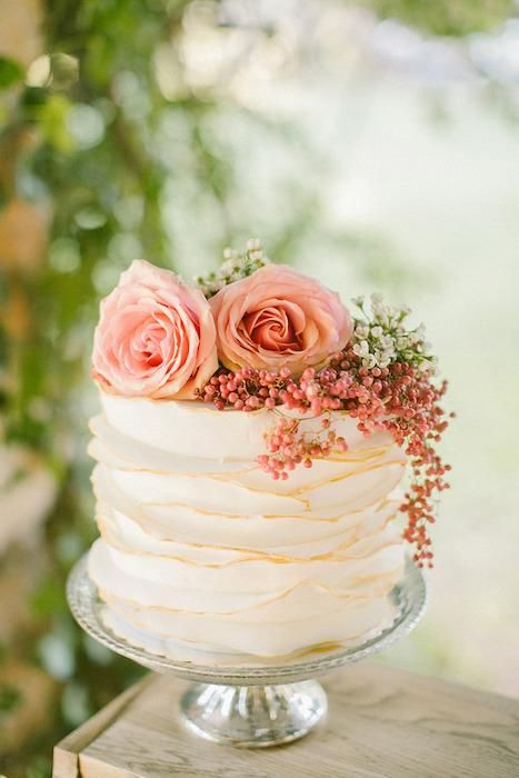a small ruffle wedding cake with gold touches and real blooms and berries on top