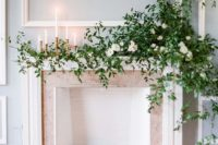 15 a subtle fireplace backdrop with candles around and on the mantel, with lush greenery and white blooms