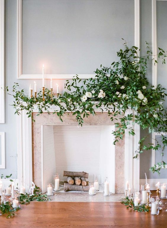 a subtle fireplace backdrop with candles around and on the mantel, with lush greenery and white blooms