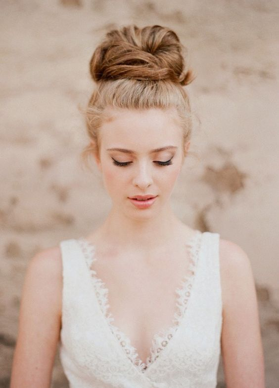 a wedding top knot with some loose hair is a chic and effortless hairstyle for a bride