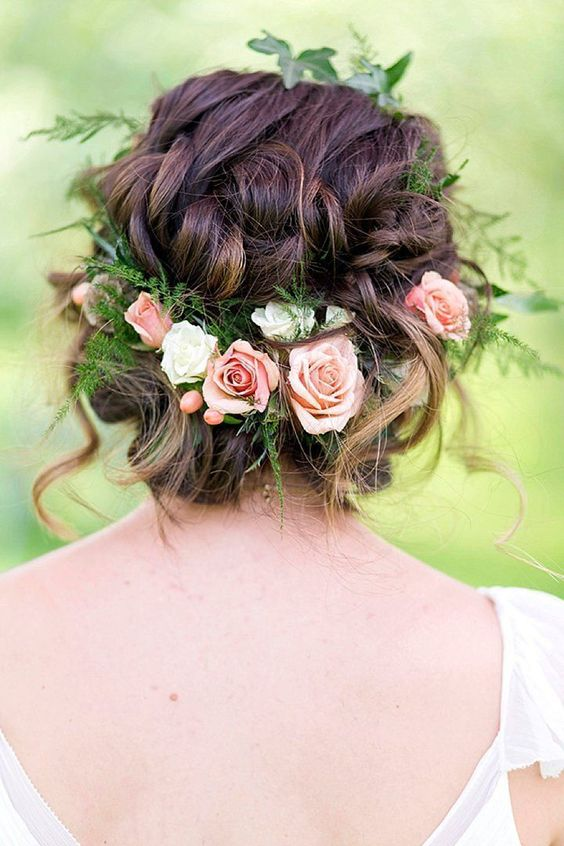 a curly braided updo with greenery and fresh blooms and some curls down for a messy feel