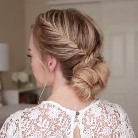 a fishtail French braid with a low bun on long hair is a great and trendy take on a usual low bun
