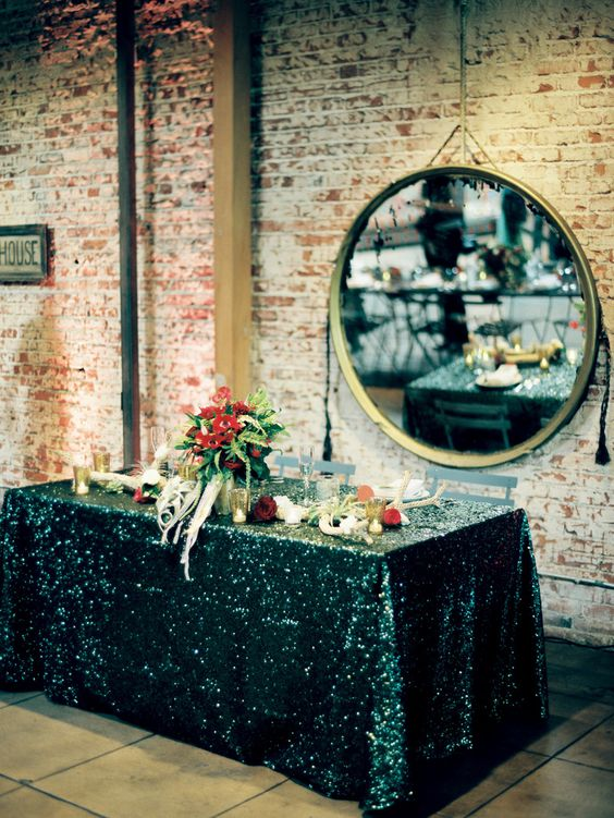 a dramatic tablescape with a black sequin tablecloth and burgundy blooms is a great idea for a moody wedding