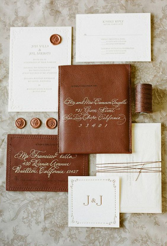 a modern rustic wedding invitation suite in white and brown leather with brown wax seals
