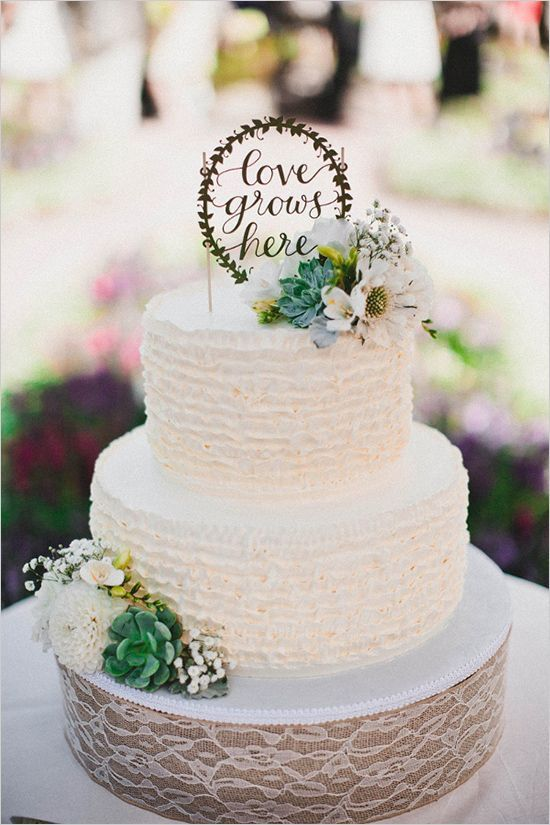 a white ruffle wedding cake decorated with succulents, neutral blooms and a calligraphy topper