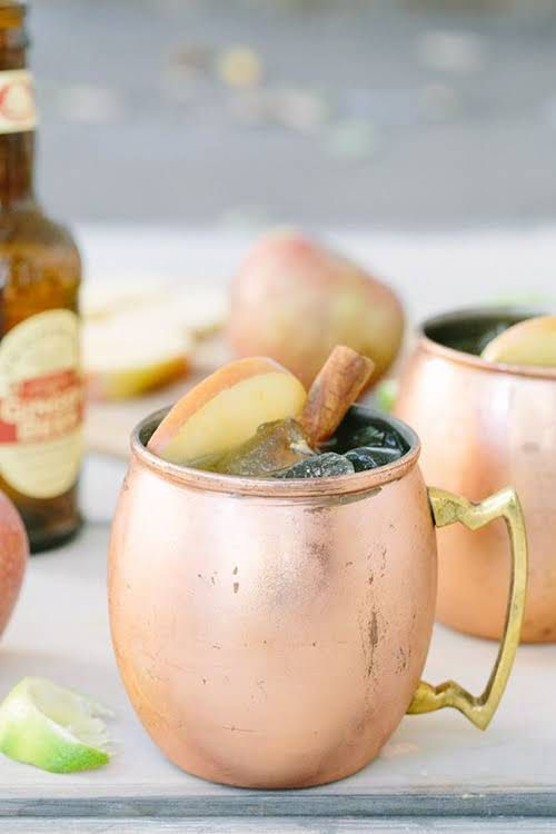 signature fall cocktails with apples and cinnamon served in copper mugs