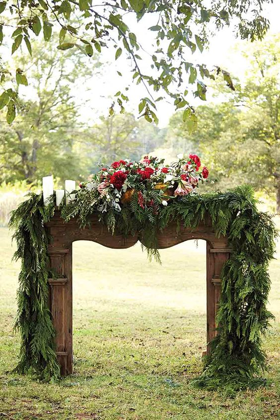 a chic rustic mantel with a lush evergreen garland, white candles and a lush red floral centerpiece