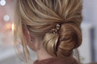 18 a chic twisted low chignon wedding hairstyle with a bump, locks down and a rhinestone hairpin