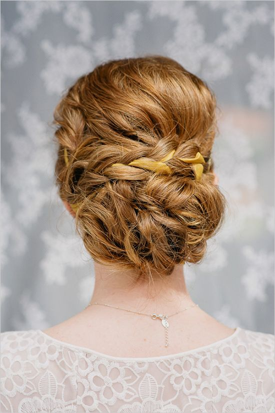 a fully braided low bun with a bump and a touch of mess for a chic boho-inspired bridal look