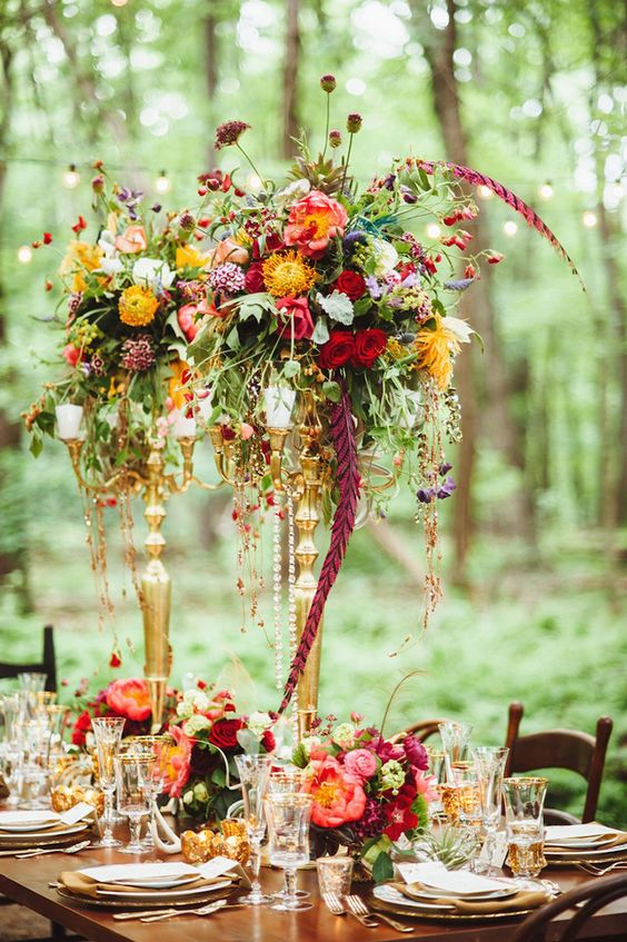 a vibrant wedding centerpiece with pink, red, yellow and orange blooms, greenery, feathers and candles
