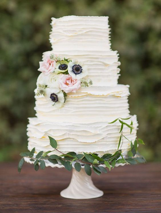 an elegant white ruffle wedding cake decorated with greenery and white and blush blooms