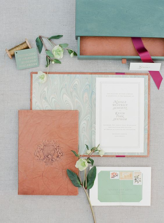 custom invitations in green wooden boxes with a leather-bound book and Italian paper