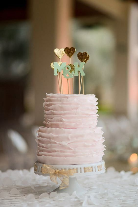 a blush ruffle wedding cake with multiple gold glitter heart toppers and monogram ones