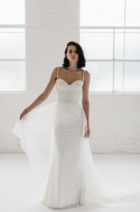 a bustier sheath wedding dress on straps with a lace bodice, a plain skirt and an airy overskirt