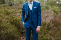 19 a fashionable look with a bright blue three-piece suit, white sneakers and a bright printed bow tie