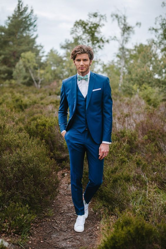 a fashionable look with a bright blue three piece suit, white sneakers and a bright printed bow tie