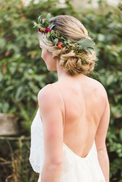a low braided updo with greenery and little colorful blooms tucked into the hairstyle