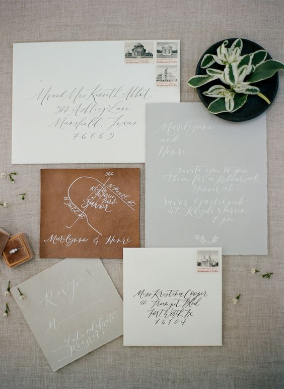 neutral wedding invitation suite with calligraphy and a map painted on a piece of leather