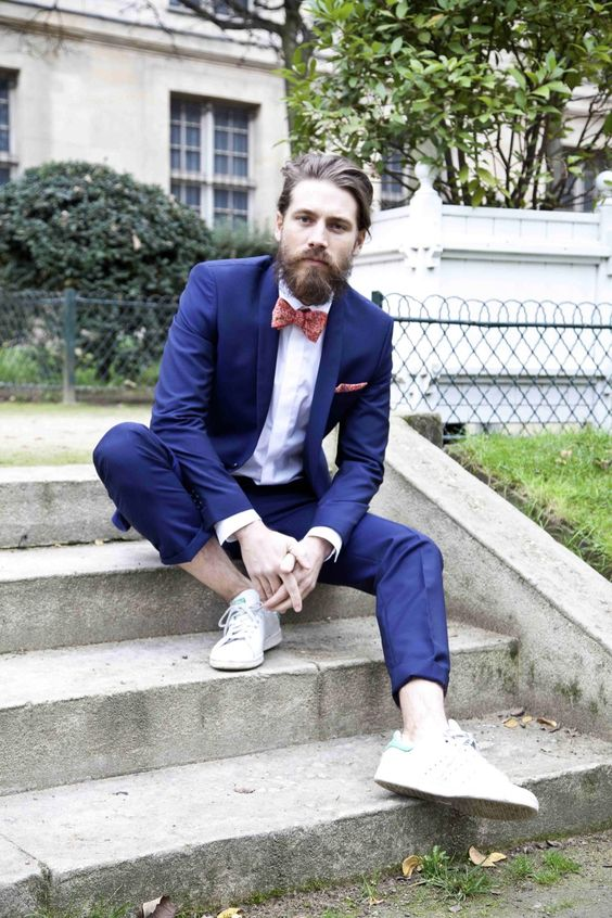 a bright blue wedding suit, no socks, white sneakers and a coral printed bow tie