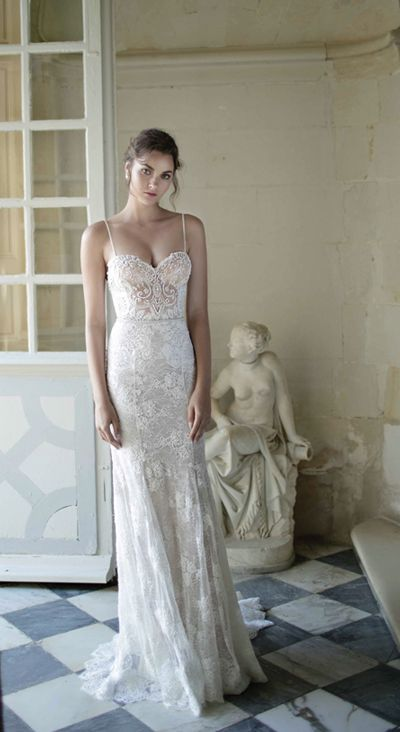 a chic lace sheath wedding dress with spaghetti straps and a small train and an accented waist