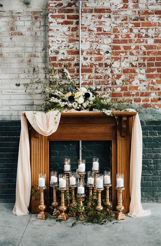 a faux wooden mantel with an airy runner, contrasting florals on the mantel and candles inside it