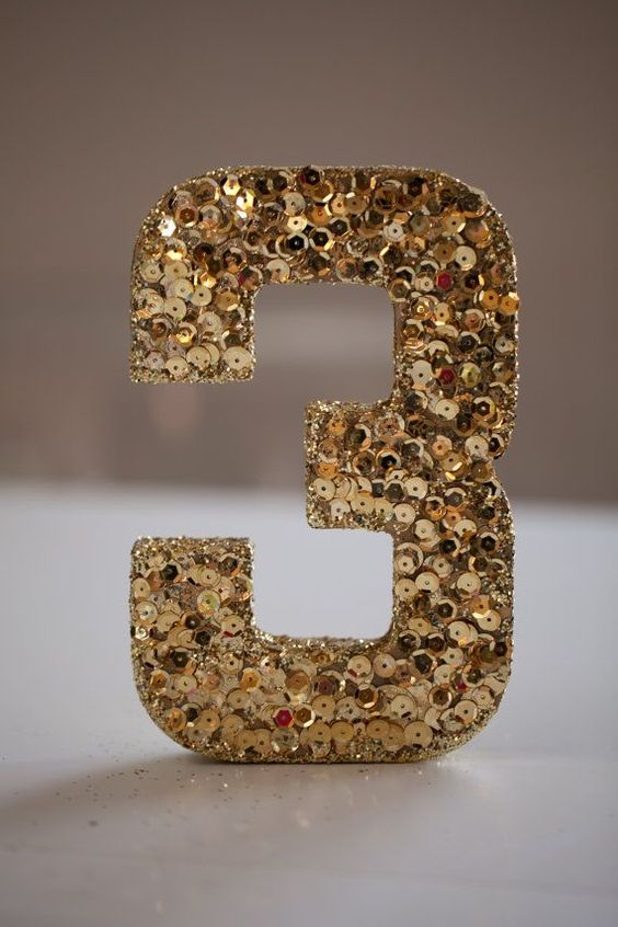 a gold sequin table number is a chic idea for many wedding themes and styles