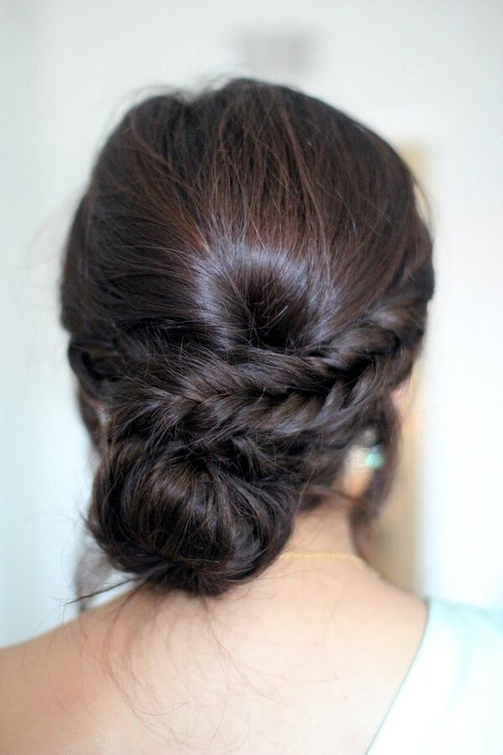 a low bun with a side braid and a bump for a whimsy take on a usual low bun hairstyle
