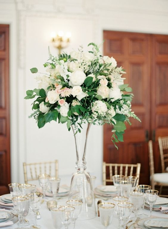 an elegant wedding centerpiece of white and blush blooms plus greenery in a tall clear glass vase