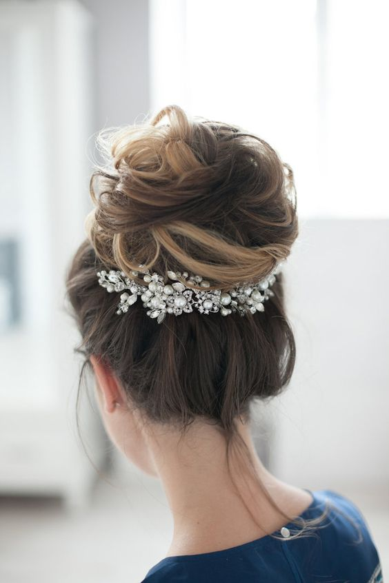a dimensional messy top knot is accented witha  large pearly hairpiece for a more refined feel