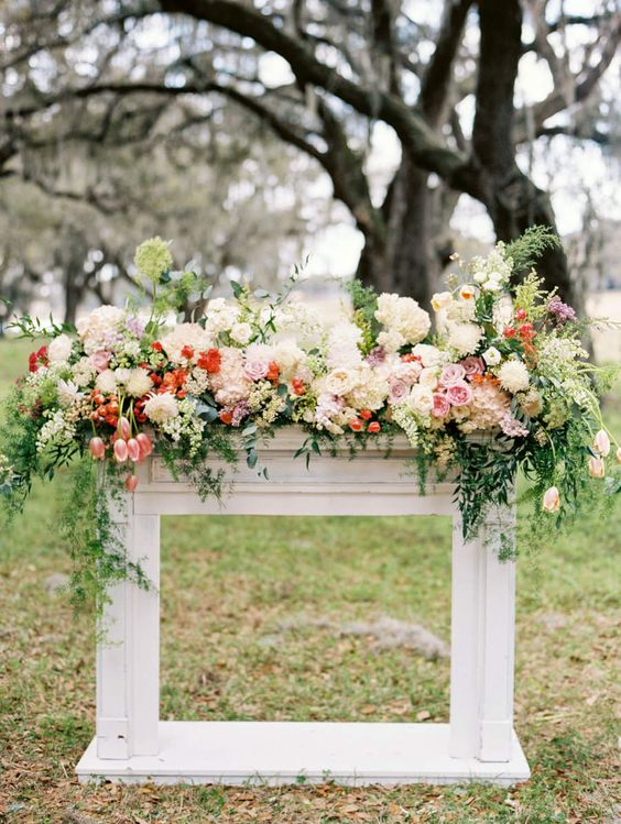a floral arbor mantel with lush blooms and cascading greenery for a chic and elegant feel