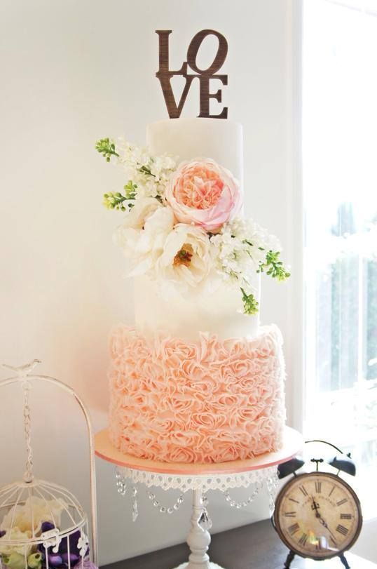 a gorgeous wedding cake with a white layer and a blush ruffle one plus lush blooms on top for a glam feel