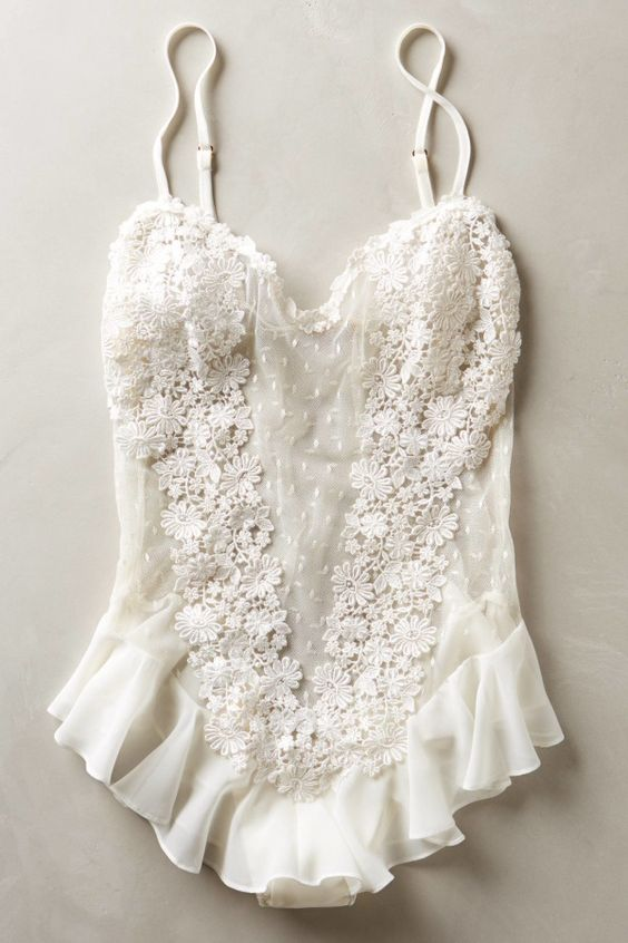 a romantic white bodysuit with ruffles, lace appliques and sheer parts