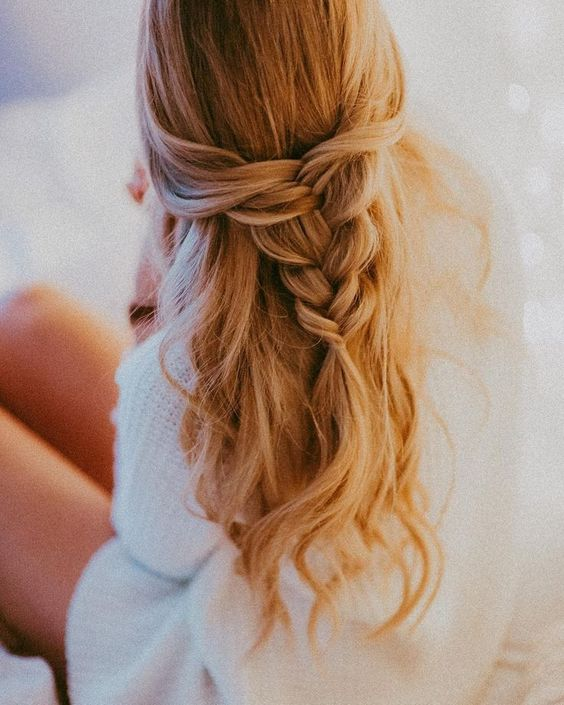 a half updo with a loose braid and waves down is a great romantic idea for a wedding guest
