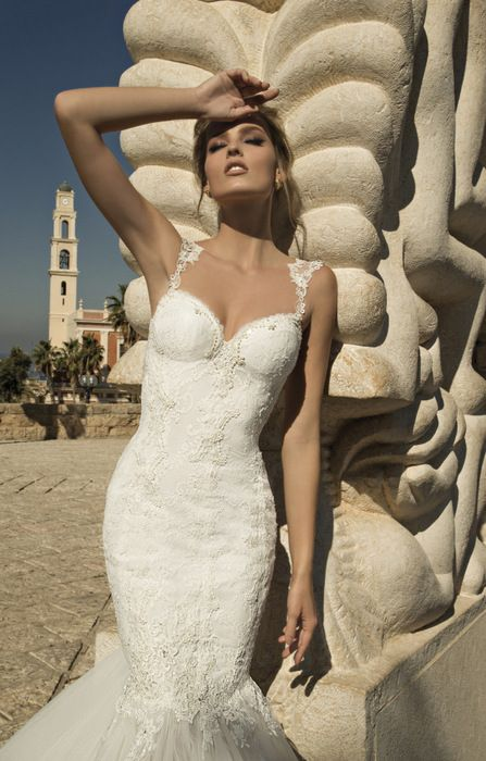 a lace embellished mermaid wedding dress with lace straps and a train for a luxurious look