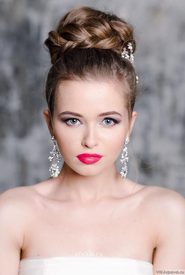 a large braided top knot accented with a rhinestone hairpiece and matching jewelry for a glam feel