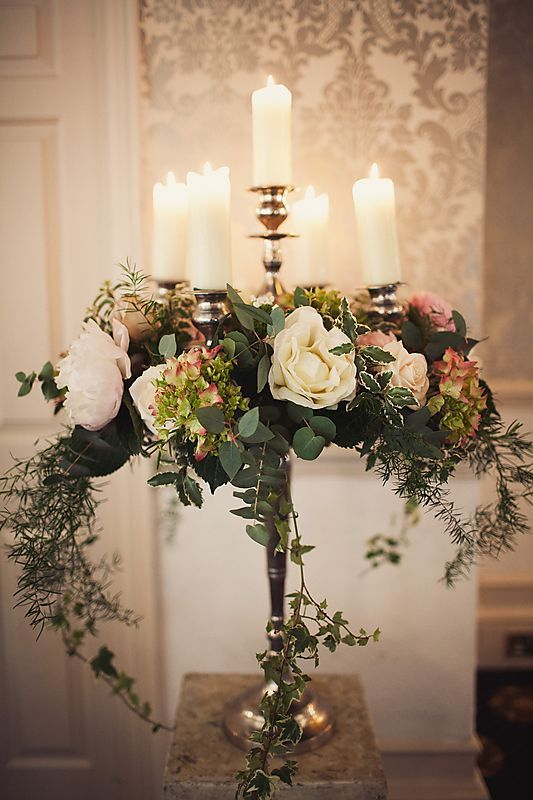 a luxurious tall candelabra centerpiece with candles, blush and neutral blooms and cascading greenery