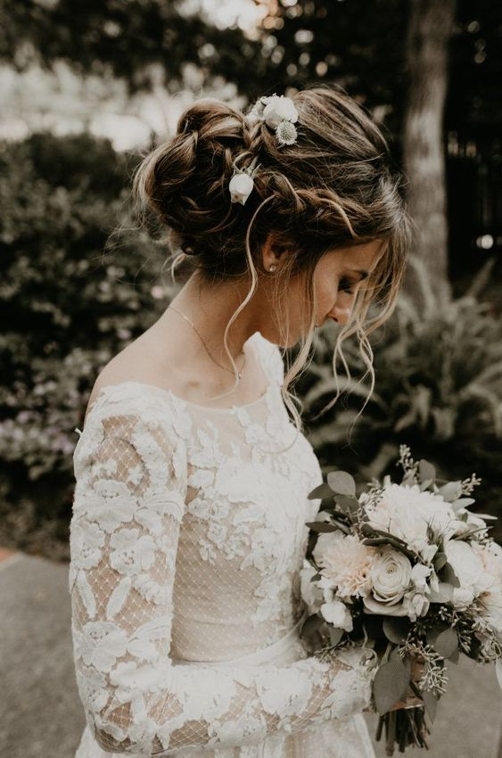 a messy twisted and braided updo with a braided halo and some curls down for a boho bride