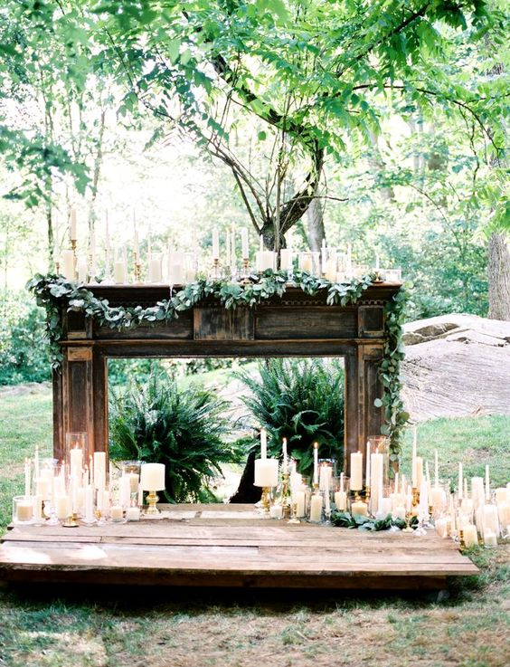 a romantic mantel with candles around, on the mantel and a greenery garland for a gorgeous backdrop