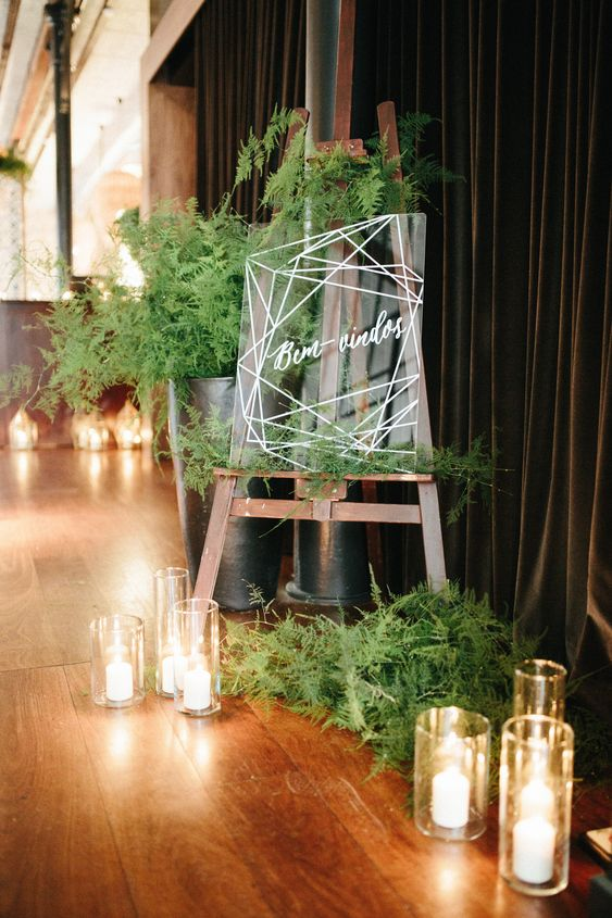 fern wedding decor with an acrylic sign, candles and lots of candles is chic and modern