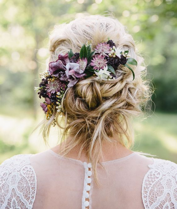a messy twisted low updo with some hair down and moody fresh blooms plus a bump