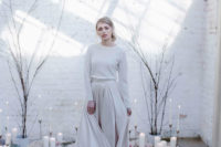 23 a minimalist wedding ensemble with a plain pleated skirt and a neutral top with long sleeves