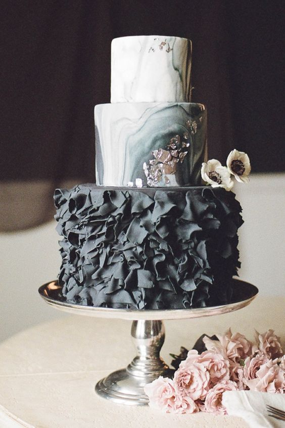 a moody glam wedding cake with marble layers and a black ruffle layer plus silver leaf touches