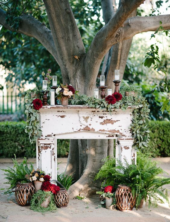 a shabby chic mantel decorated with candles, greenery, blooms, candle lanterns and foliage