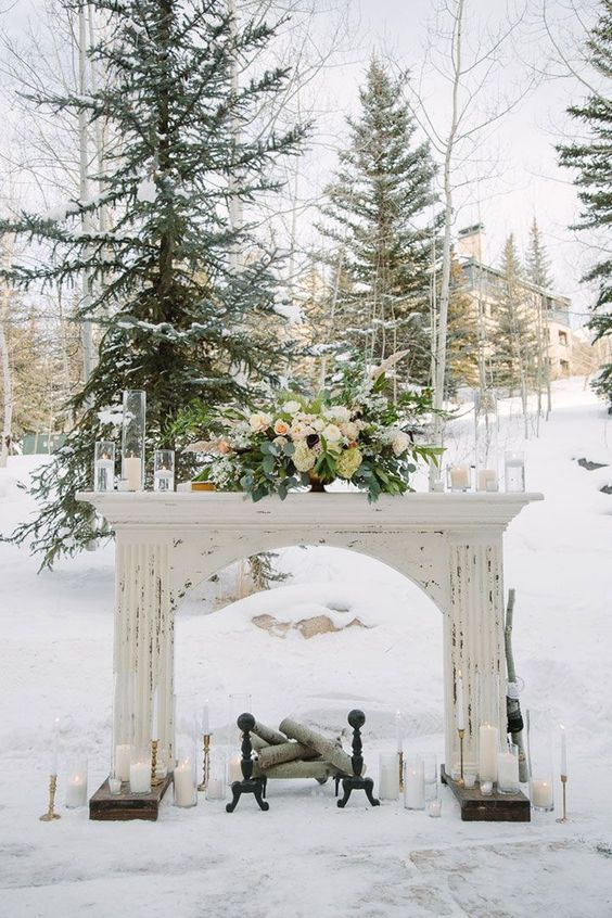 a shabby chic white mantel with candles, a lush pale centerpiece with greenery and firewood inside